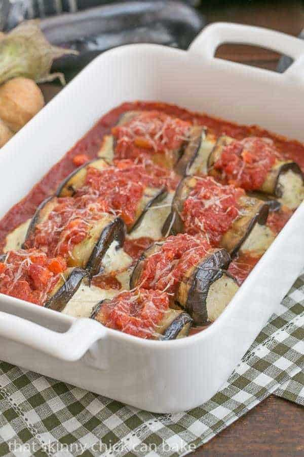 Eggplant Rollatini lined up in a white casserole dish