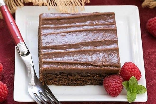 Chocolate Sheet Cake slice on a square white plate with raspberries