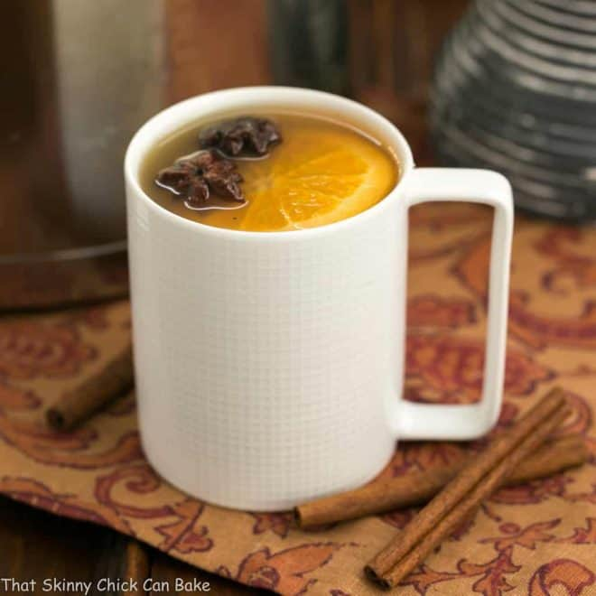 Mulled Apple Cider in a white mug with a slice of orange and star anise