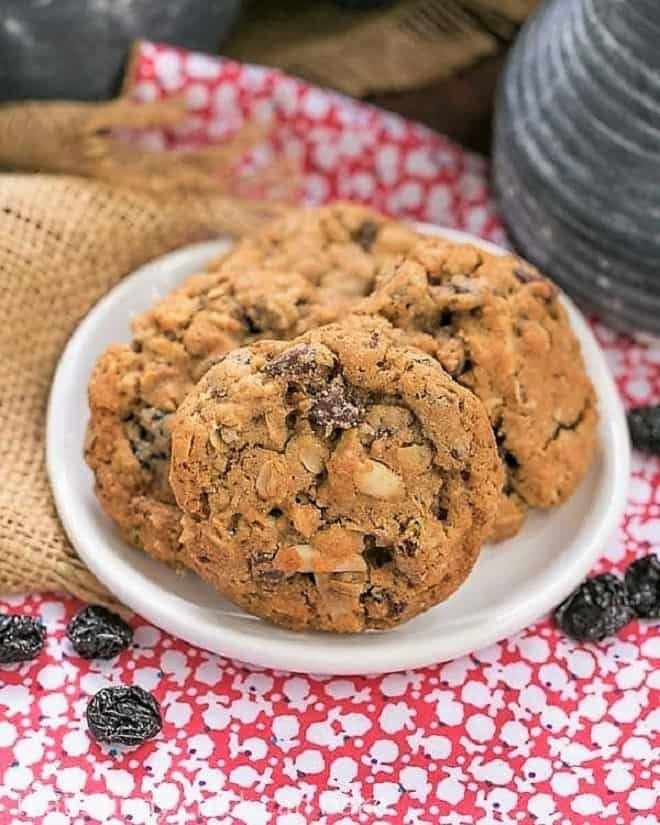 Loaded Oatmeal Cookies arranged on a small white ceramic plate with dried cherries