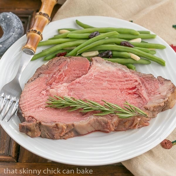 Slice of rare Classic Prime Rib on a white plate