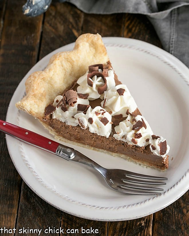 Overhead view of a slice of French Silk Pie on a white dessert plate with a red handled fork