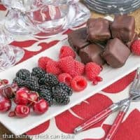 Chocolate Dipped Cheesecake Bites on a white tray with fruit