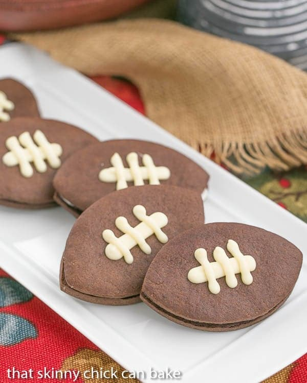 plate of Chocolate Football Cookies - Chocolate cut-out cookies filled with buttercream and caramel!