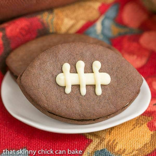 Chocolate Football Cookies - Chocolate cut-out cookies filled with buttercream and caramel!