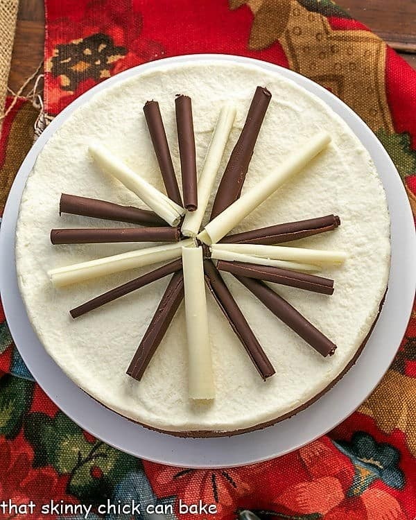 Overhead view of a beautiful white chocolate and milk chocolate Layered Mousse Cake on a white cake plate