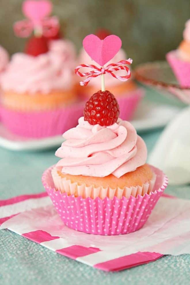 Pink Velvet Raspberry Cupcakes in pink wrappers topped with frosting and a raspberry