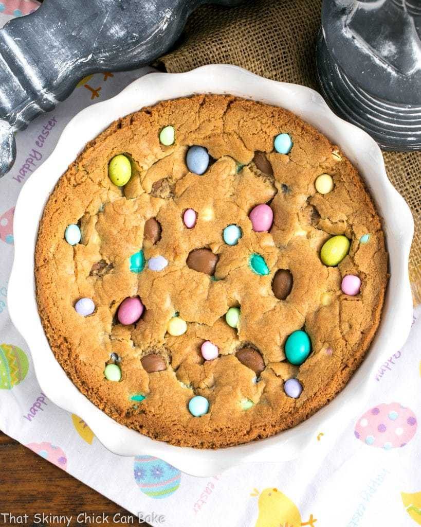 overhead image of a large cookie cake studded with various types of Easter candy