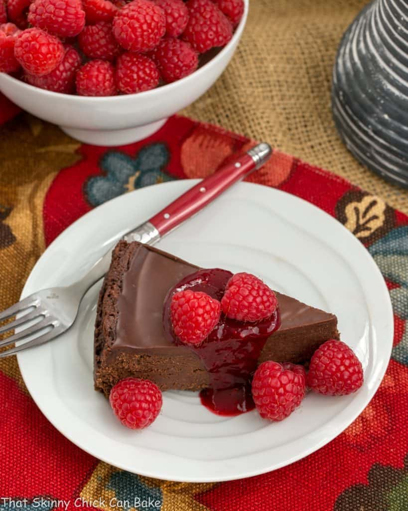 overhead image of gluten free Chocolate Torte on a white plate, garnished with chocolate ganache and raspberries