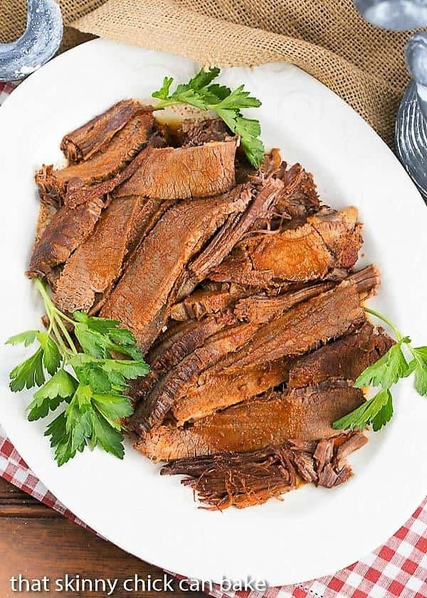 white serving platter filled with slices of Oven Braised Texas Brisket