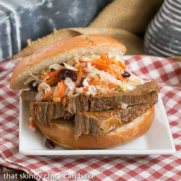 Oven Braised Texas Brisket on a large kaiser bun, topped with coleslaw
