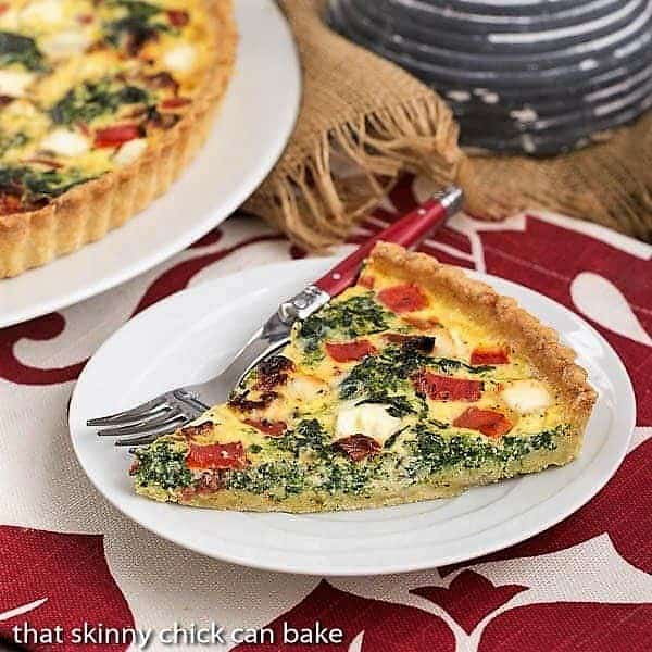 Sun-dried Tomato and Spinach Quiche slice on a white plate with a red handled fork
