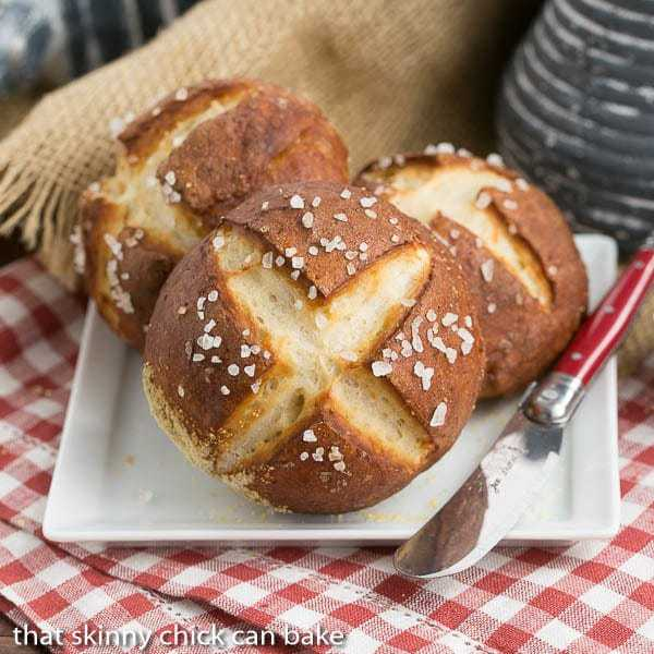 Pretzel Rolls on a square white plate with a red handled knife