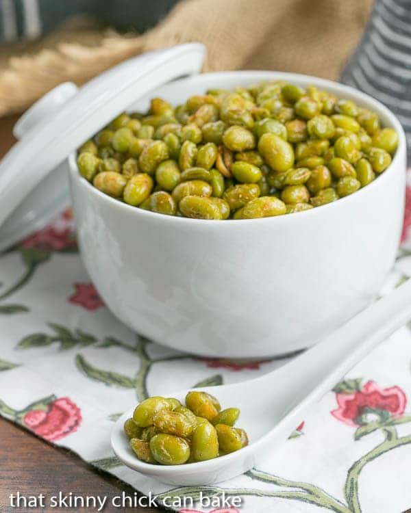 Roasted Creole Edamame in a white ceramic bowl with a spoonful in the foreground