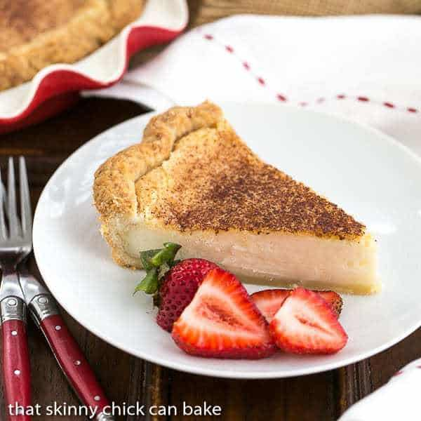 A slice of Hoosier Sugar Cream Pie on a white plate with strawberry slices
