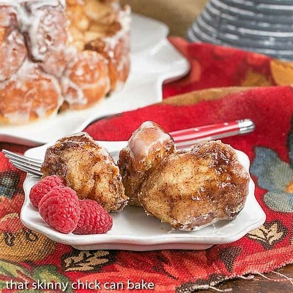 Cinnamon Bubble Roll pieces on a small white plate with fresh raspberries