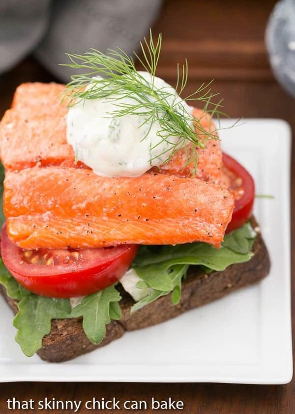 Open-Faced Salmon Sandwiches with Herb Cucumber Relish on a square white plate with a dollop of relish and dill sprig to garnish