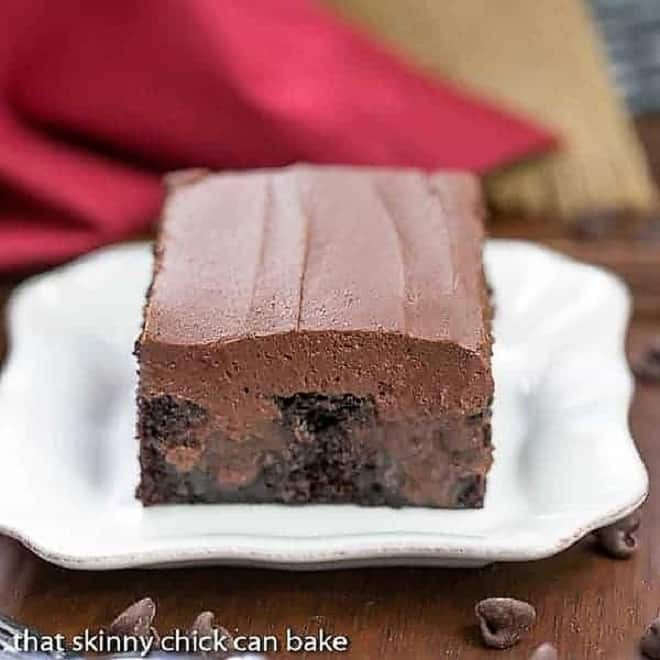 A slice of Triple Chocolate Poke Cake  on a square white plate