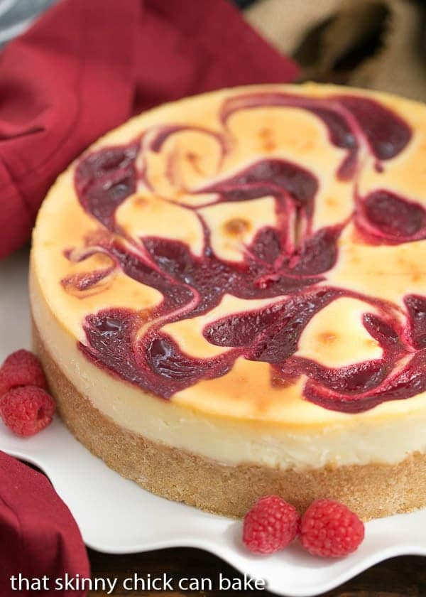 White Chocolate Raspberry Swirl Cheesecake on a wavy, white serving dish