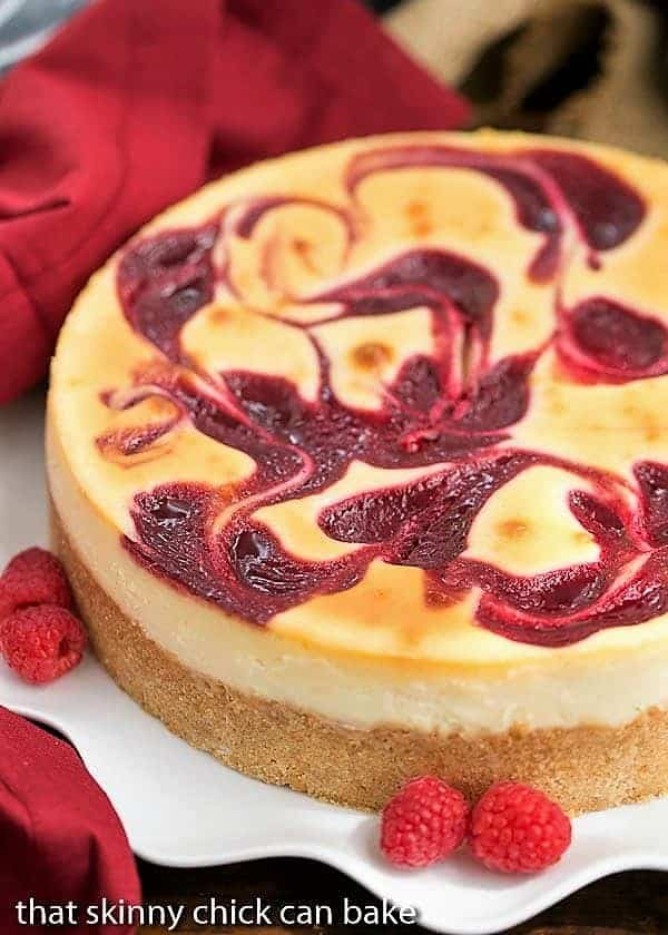 White Chocolate Raspberry Swirl Cheesecake on  a white plate garnished with fresh raspberries