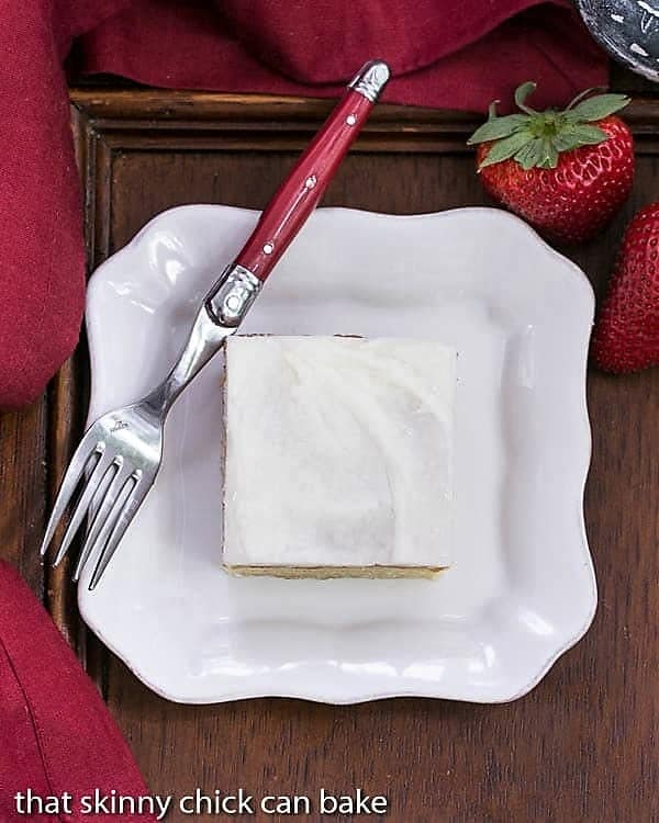 Overhead view of a slice of white sheet cake on a white plate with a red handled fork
