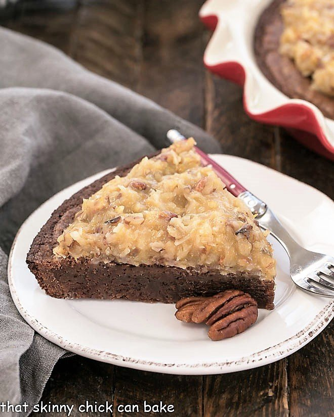 Slice of German Chocolate Brownie Pie on a white plate with a couple of pecans for garnish in front of a red pie plate
