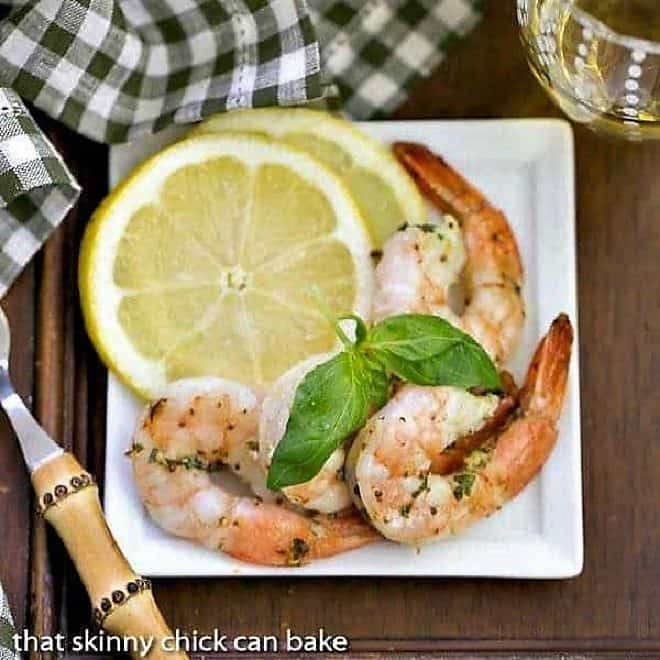 Grilled Shrimp Scampi on a square white plate with basil and lemon slices