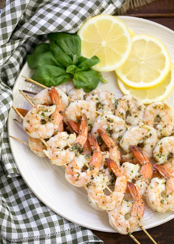 Grilled Shrimp Scampi skewered and served on a white platter with lemon slices