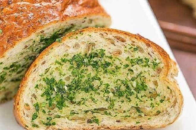 Herb Garlic Bread slice next to loaf on a white platter