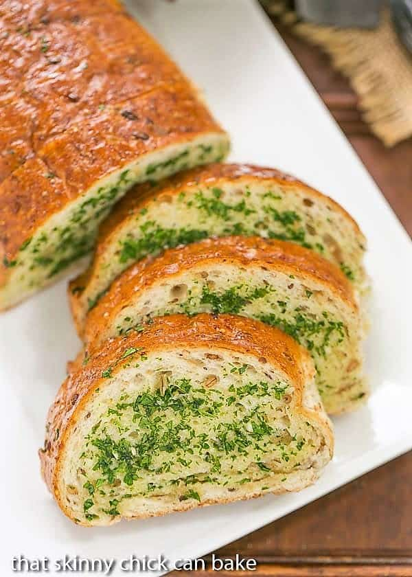Overhead view of slices of Herb Garlic Bread on a white platter