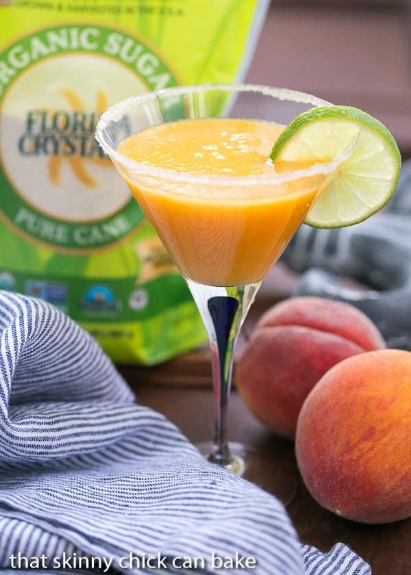 Peach Margaritas in a martini glass garnished with a slice of lime