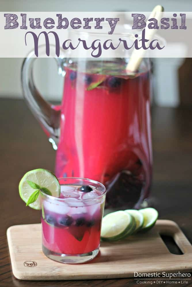 Blueberry Basil Margaritas in a pitcher with a glass garnished with lime in the foreground