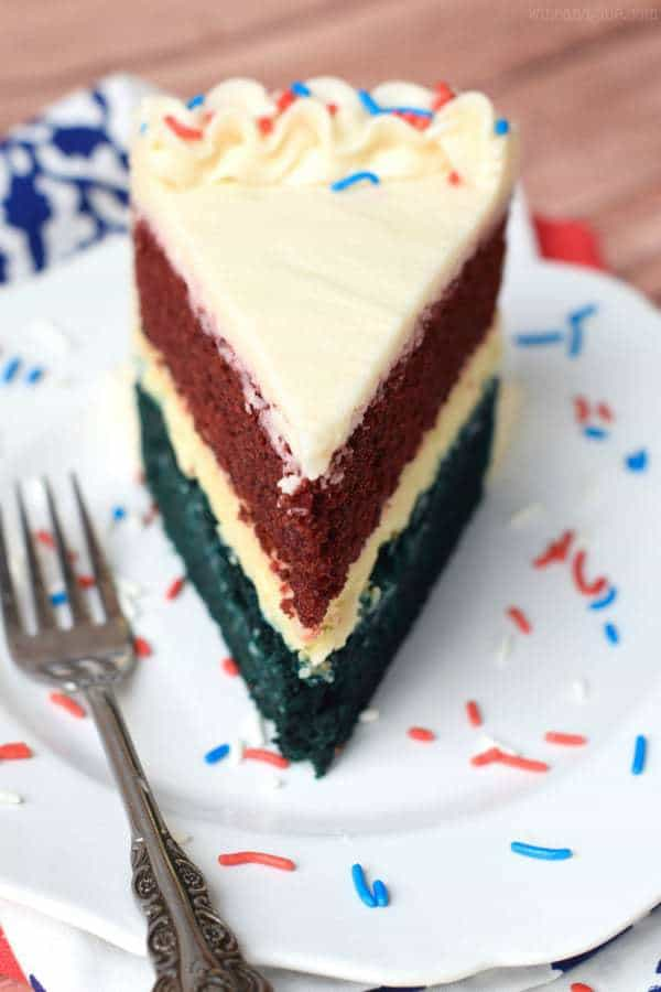 Red White and Blue Velvet Cheesecake Cake on a white plate with red white and blue sprinkles
