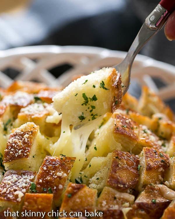 Cheesy Garlic Bread with a fork full of gooey bread on a fork