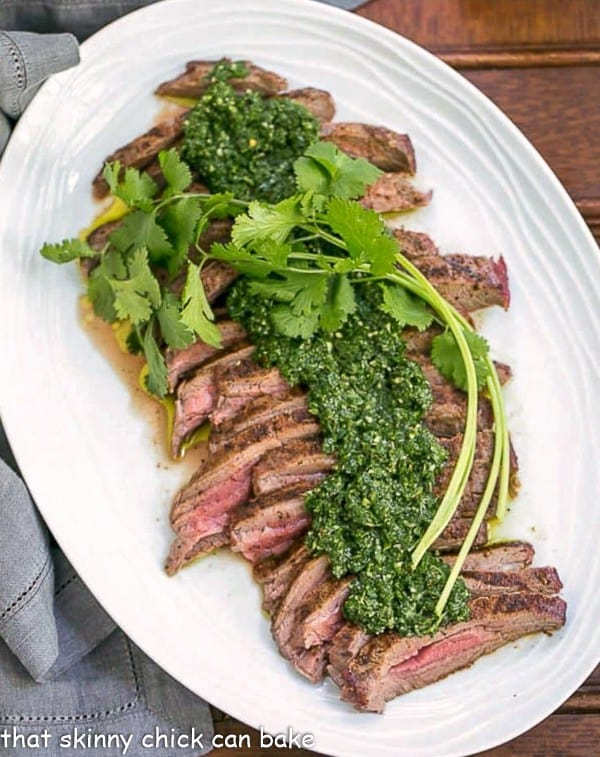 Overhead view of Grilled Flank Steak with Chimichurri Sauce on a white oval platter