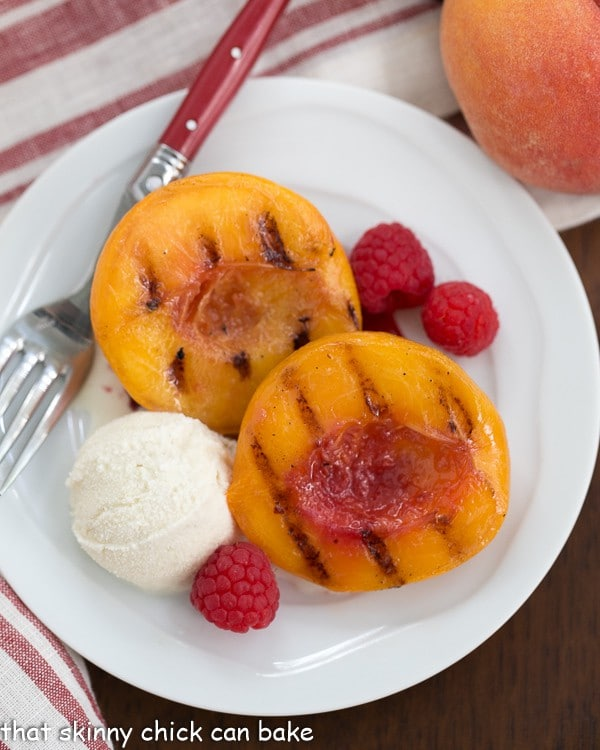 Overhead view of Grilled Peach Melba on a white plate with a fork and scoop of ice cream