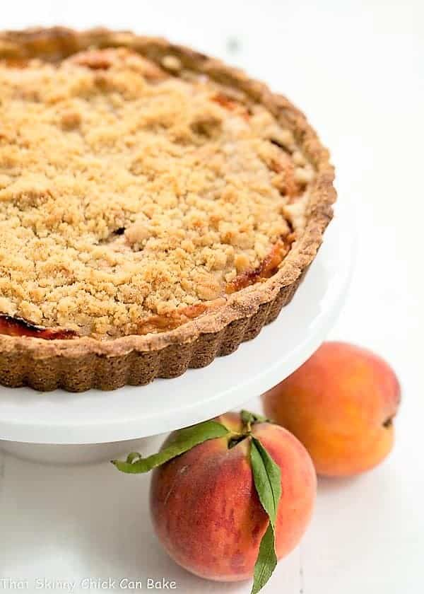 Streusel Topped Peach Tart on a white cake stand