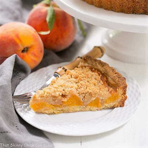 Slice of Streusel Topped Peach Tart on a white dessert plate