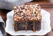Turtle Poke Cake | A marvelous chocolate cake infused with caramel and topped with buttercream, pecans and chocolate chips!