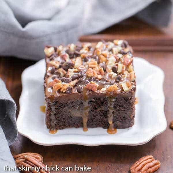 Turtle Poke Cake   A marvelous chocolate cake infused with caramel and topped with buttercream, pecans and chocolate chips!