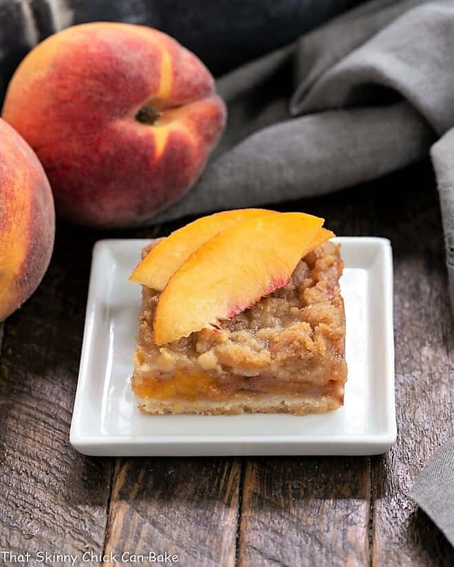 Fresh Peach Pie Bar on a white plate topped with peach slices