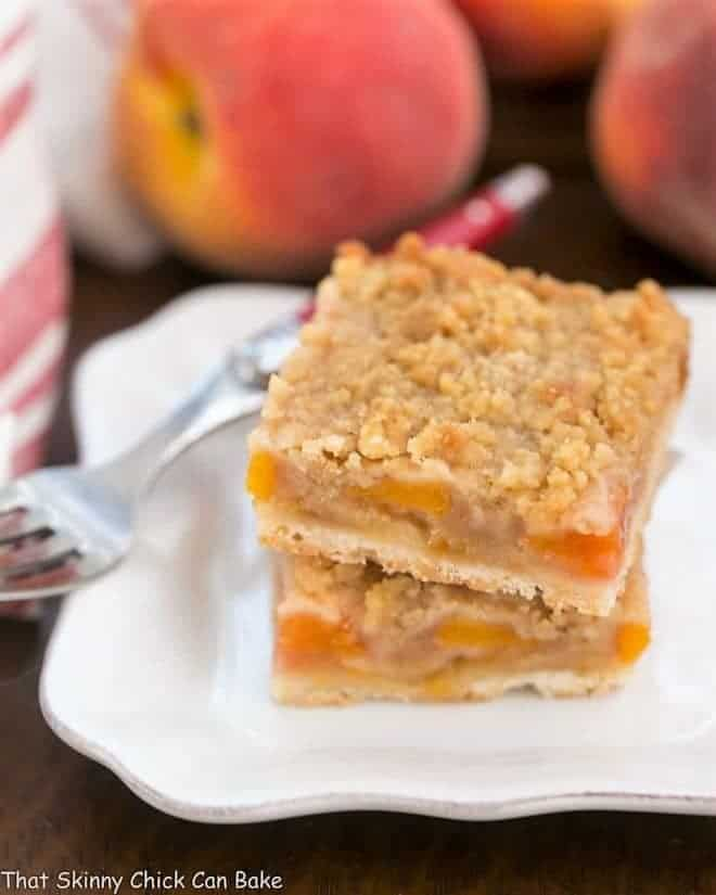 Fresh Peach Pie Bars stacked on a white square plate with a fork