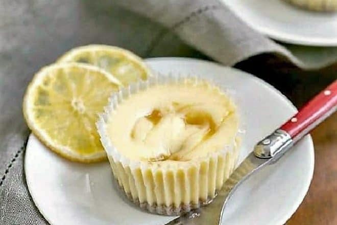 Lemon Curd Mini Cheesecakes on a white plate with dried lemon slices and a fork