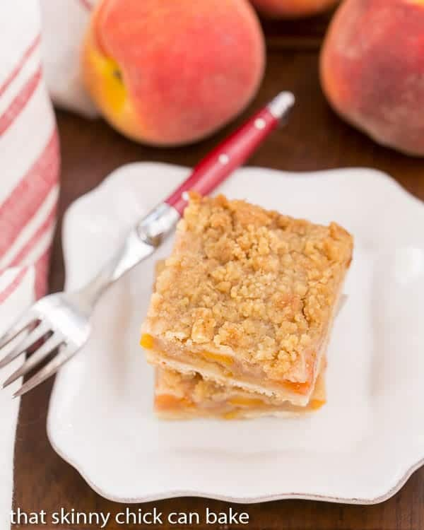 Fresh Peach Pie Bars stacked on a white plate with a red handled fork