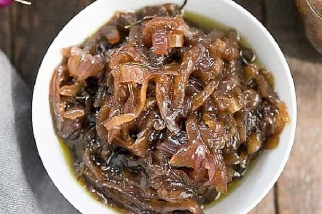 Overhead view of onion confit in a white ceramic bowl