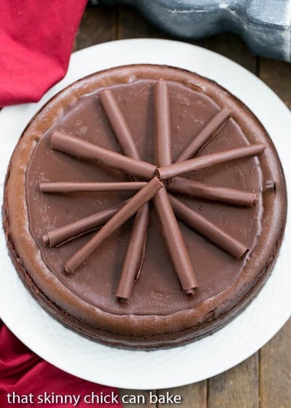 Overhead view of a Triple Chocolate Cheesecake on a white serving plate