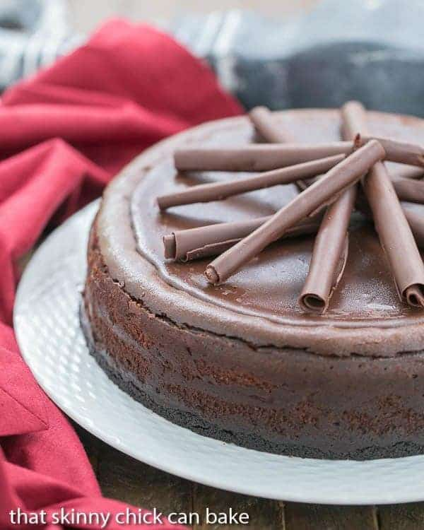 Triple Chocolate Cheesecake on a white ceramic serving plate with a red napkin