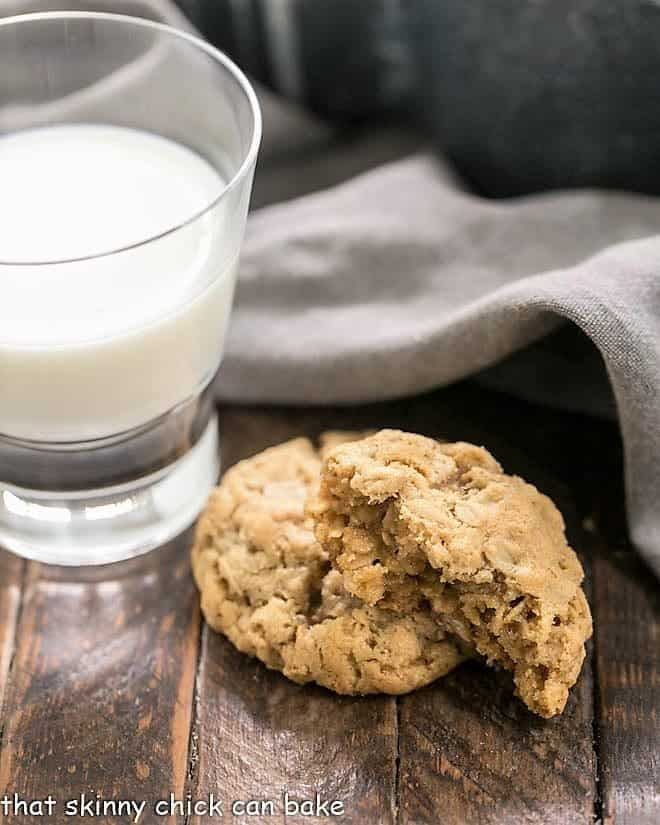 One whole and one half chewy oatmeal cookies with a glass of milk