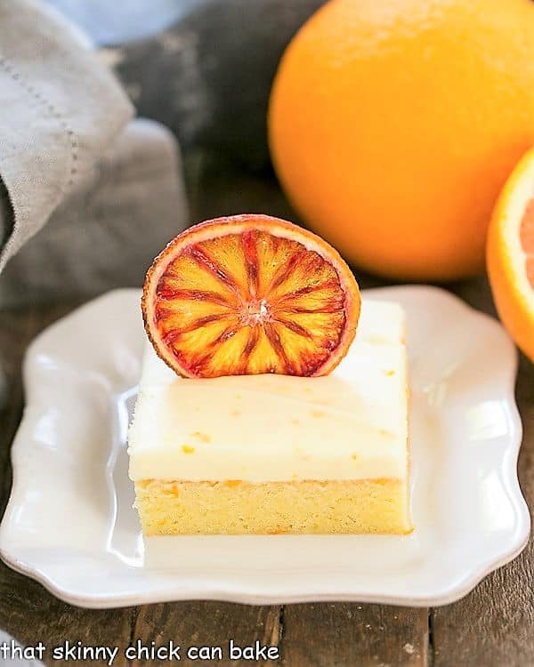 Orange Cake with Cream Cheese Frosting on a square white plate with oranges
