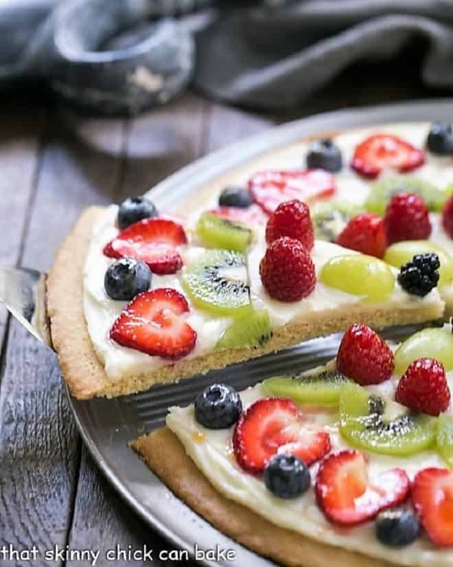 A slice of Fresh Fruit Pizza being removed from a whole pizza on a metal pizza pan
